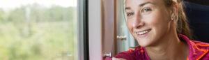 Leende kvinna åker tåg