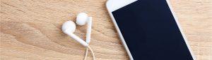 Mobiltelefon med hörlurar på ett bord